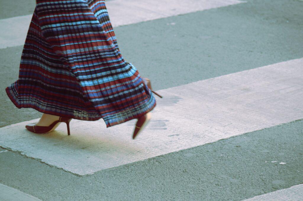 Detail of woman walking along street in heels