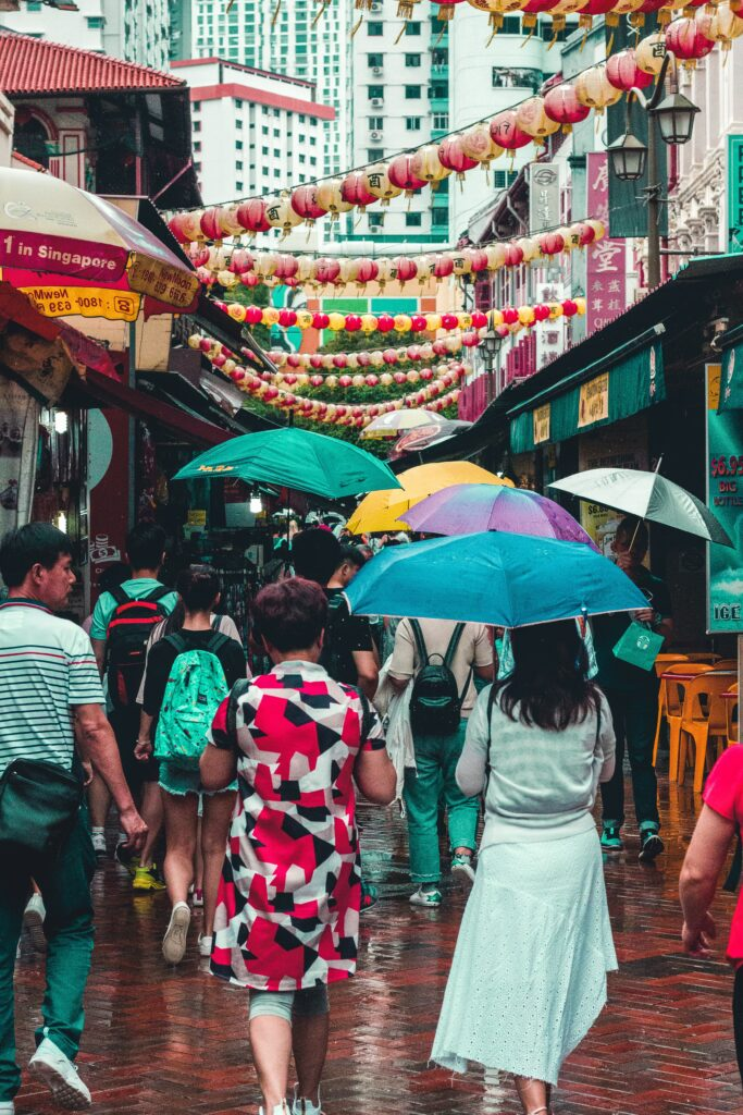 Crowded street with lanterns, shops, restaurants, and people holding umbrellas in the rain